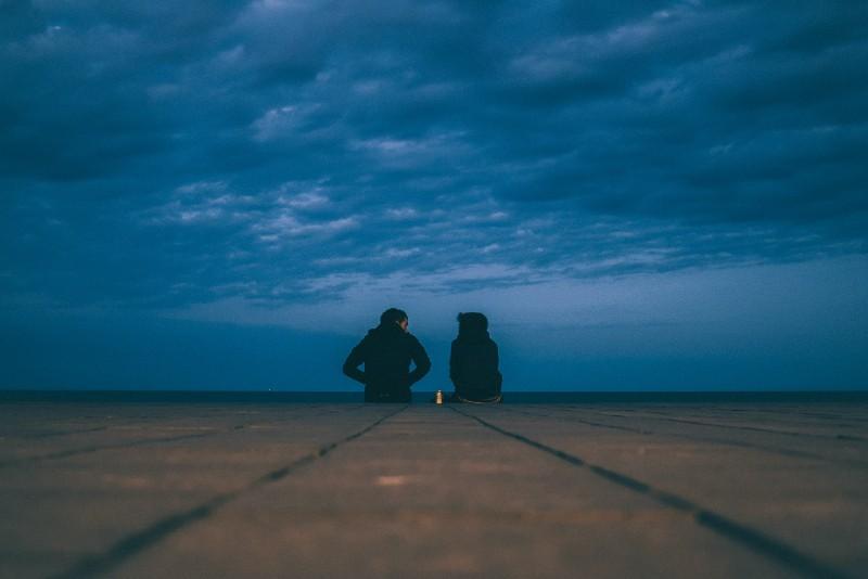 man and woman sitting on ground near sea