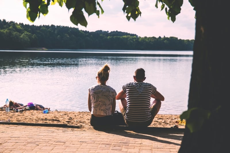 man and woman sitting on pavement near water