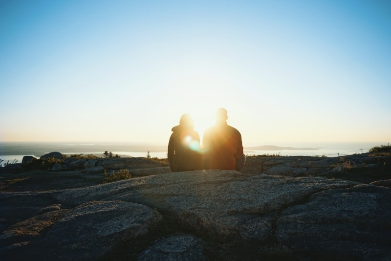 man and woman sitting on rock looking at sunrise