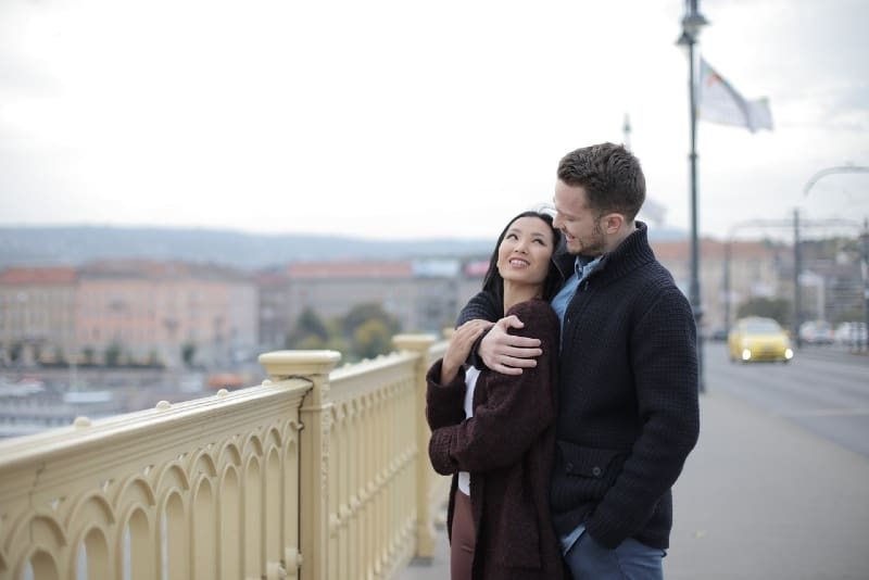 man hugging woman while standing on the bridge
