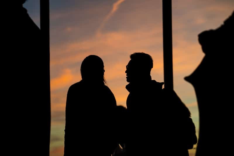 man and woman talking during sunset