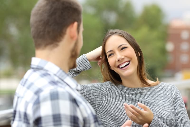 smiling woman and man sitting outdoor and talking