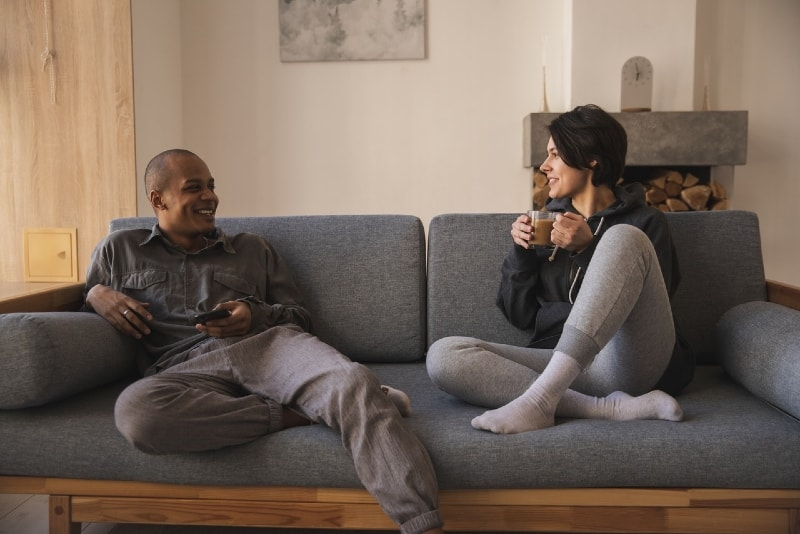 smiling man and woman talking while sitting on sofa