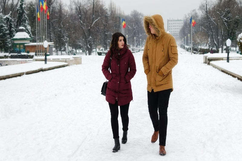 man in yellow jacket and woman walking in snow