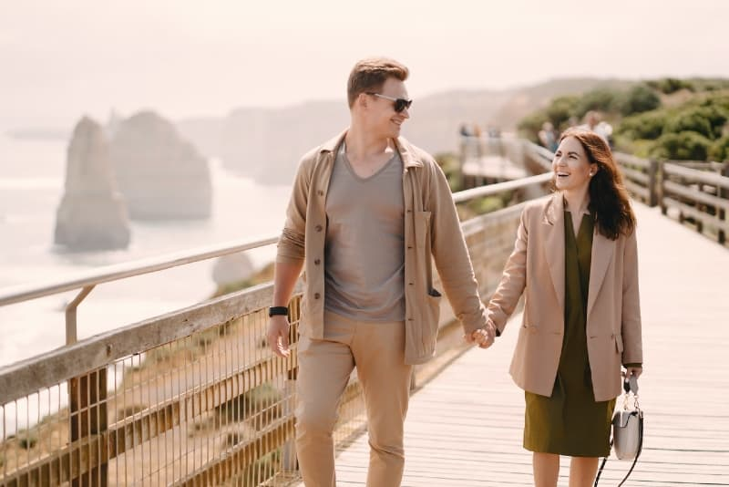smiling man and woman holding hands while walking on bridge
