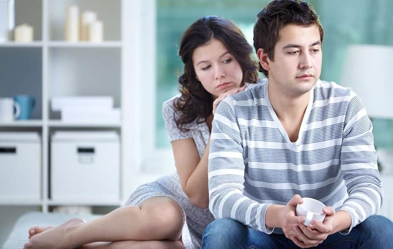 couple with problems sitting on couch inside the living room