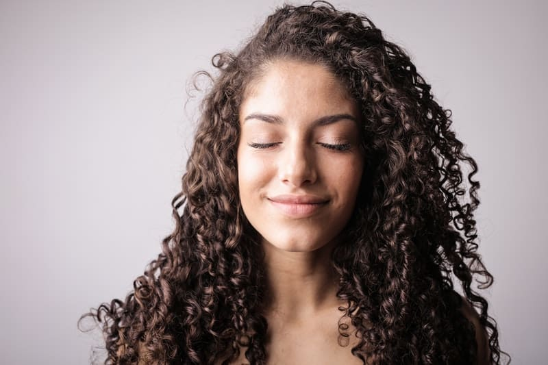 curly haired woman closing her eyes and smiling