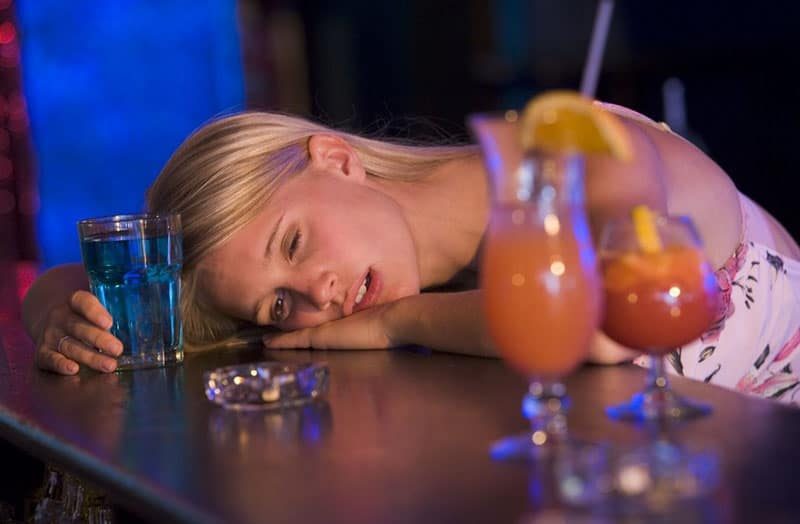 drunk young woman resting her head on the bar counter