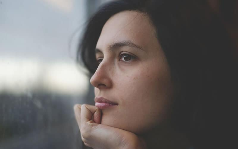 focus image of woman looking thoughtful with face resting on hand