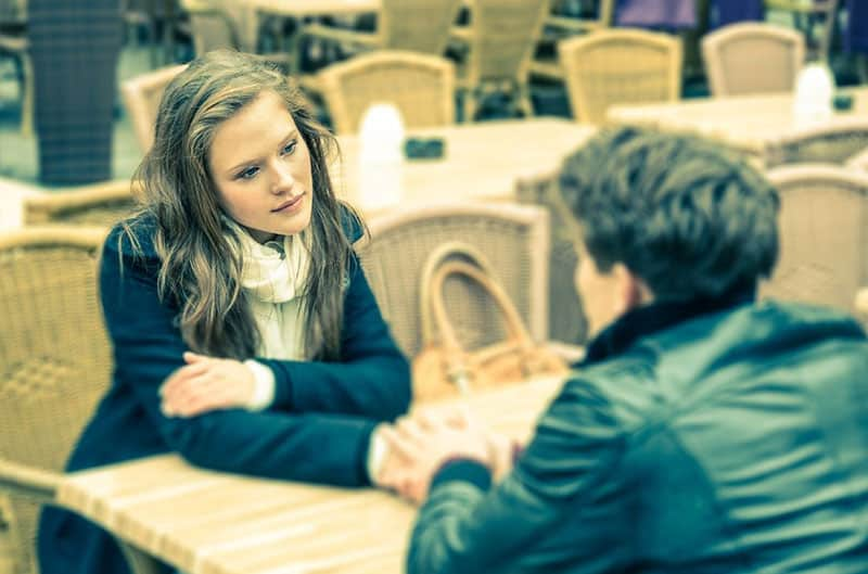 forgiving woman sitting in front of a man holding her hand inside an empty restaurant