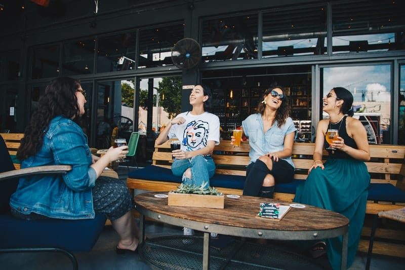 four women chatting and laughing outdoors with drinks on hand