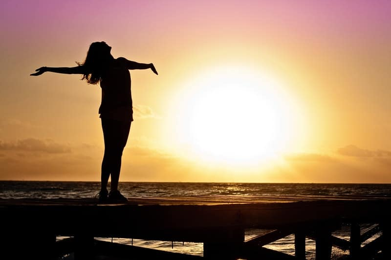 free woman spreading arms with a bright sun at the back in silhouette