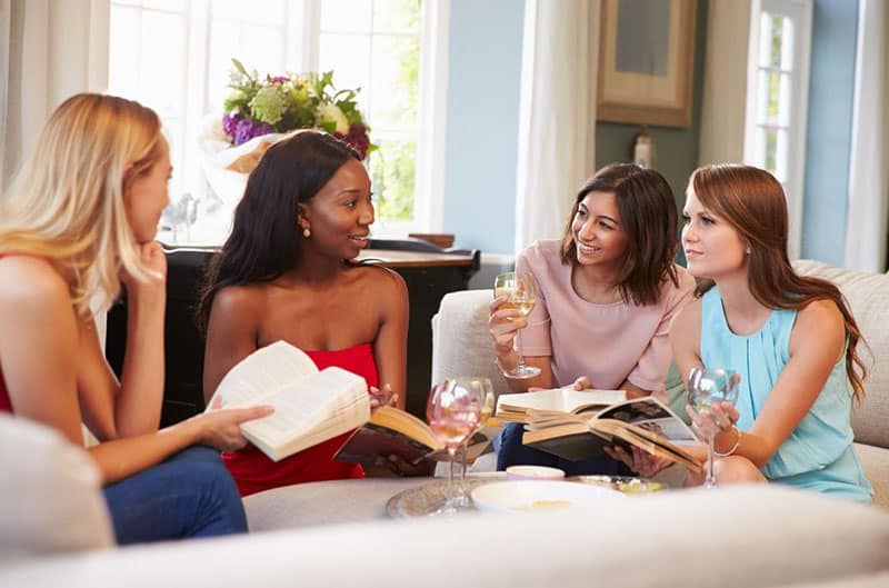 group of female friends talking about book while sitting in the living room