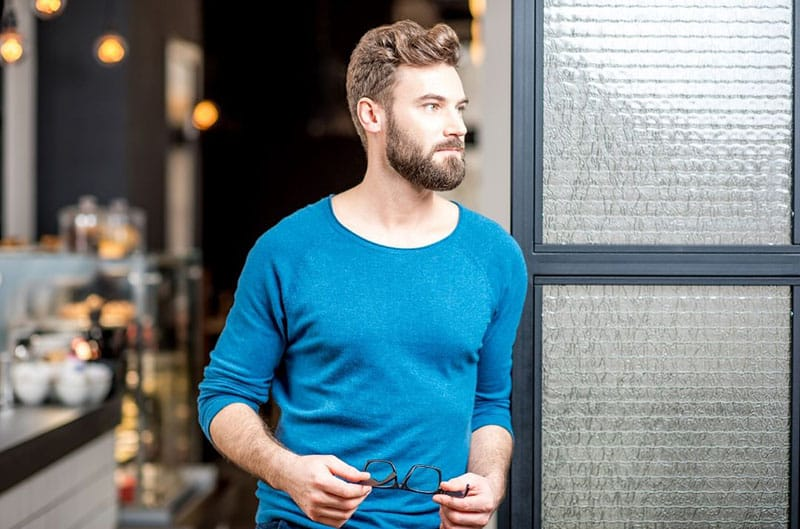 handsome guy in blue top standing in the door way holding an eyeglass