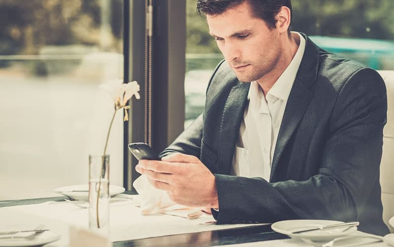 handsome man using a smartphone inside the restaurant