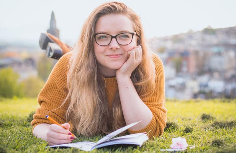 happy young woman writing on her notebook while squatting on ground
