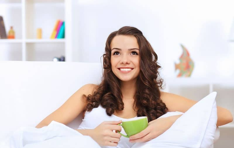 image of a young woman sitting on a couch with a green cup in the hands