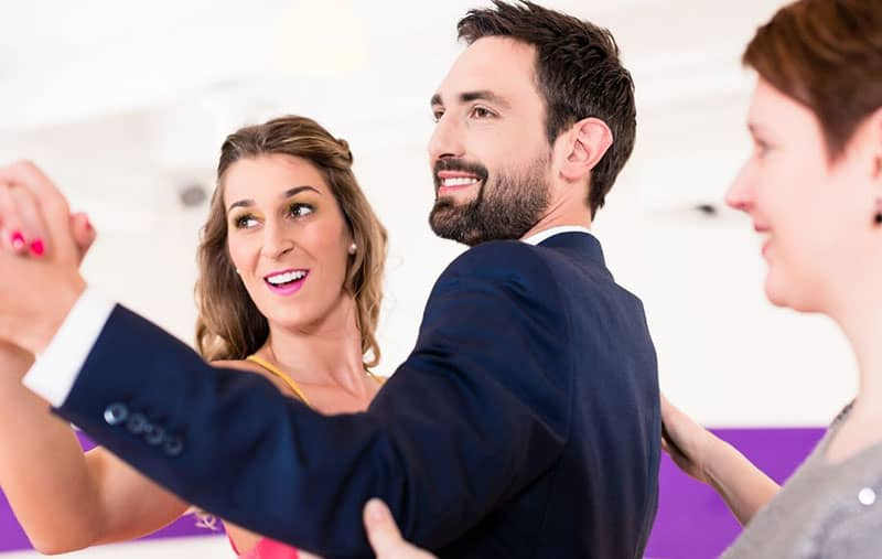 instructor in dance school teaching a couple to dance