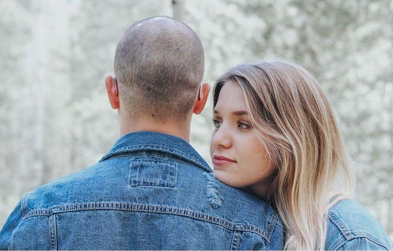 lady hugs a man wearing denim jacket outdoors