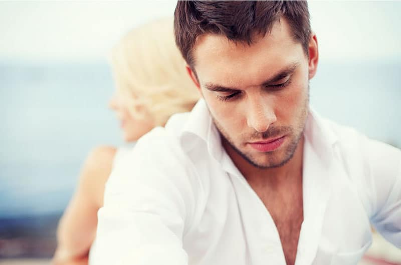man and woman back to back sitting wearing white top with man in front if the camera