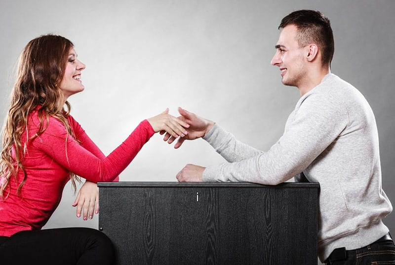 man and woman shake hands while sitting face to face and hands on the table