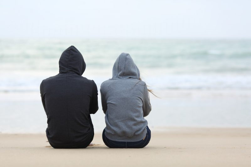 man and woman sitting on the beach talking