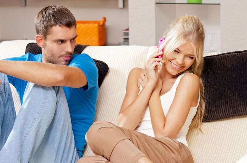 man angry with his partner answering and giggling over phone call right next to him