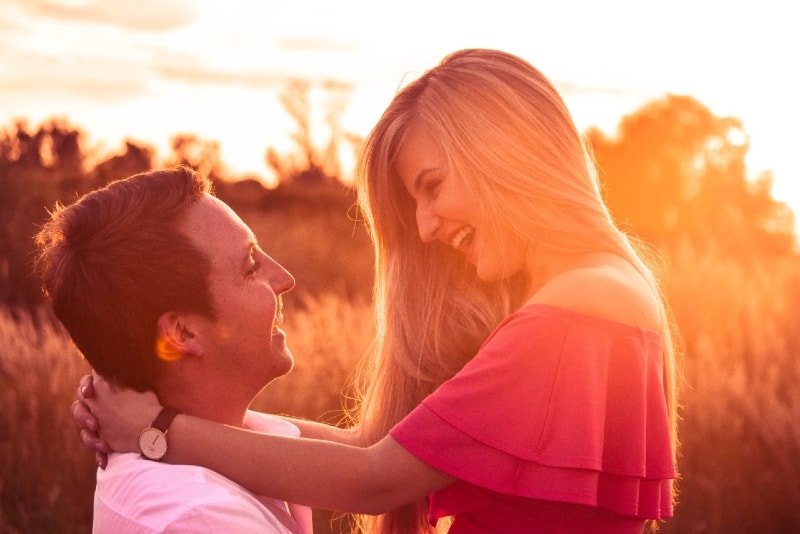 smiling man carrying woman in pink top