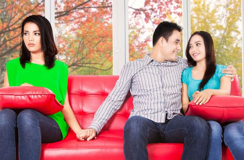 man holding hand of a woman while his other arms is wrapped around another woman sitting on the red sofa