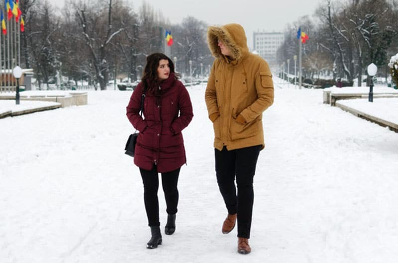 man in brown winter jacket talking and walking with a woman outdoors during winter