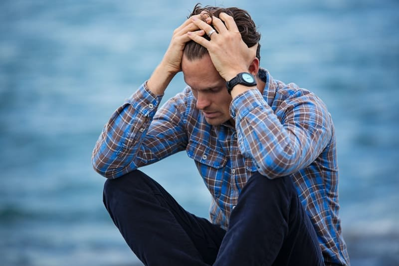 man in checkered sitting near a body of water with hands on his head feeling sad