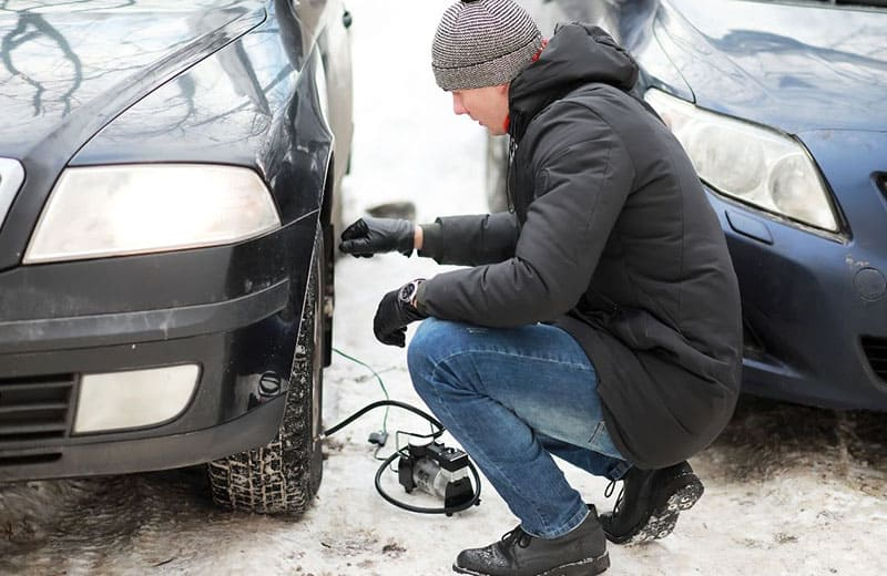 man inflating flat car tire during snowy season