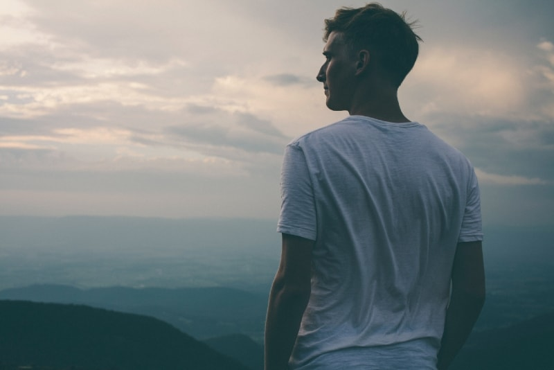 man in white t-shirt looking at mountain during sunset