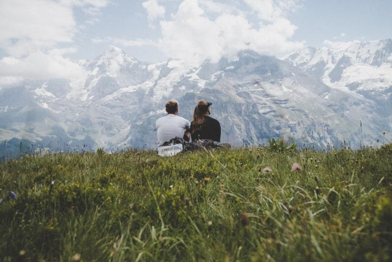 man sitting beside woman on grass facing mountain