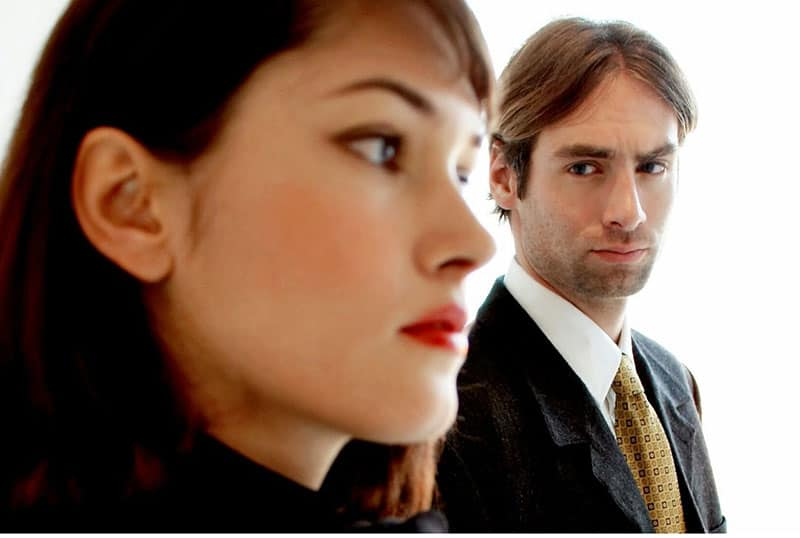man staring at a woman at a distance wearing office suit