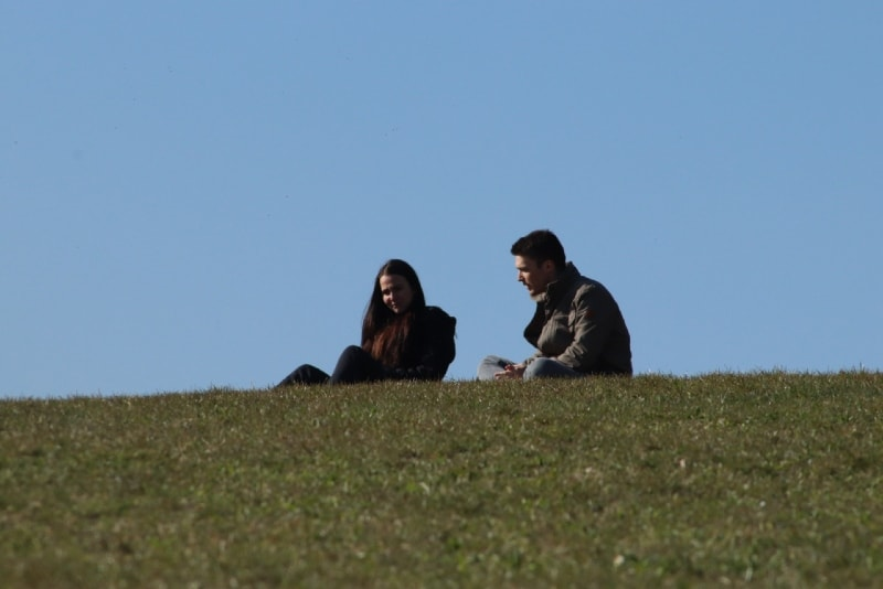 man talking to woman while sitting on grass