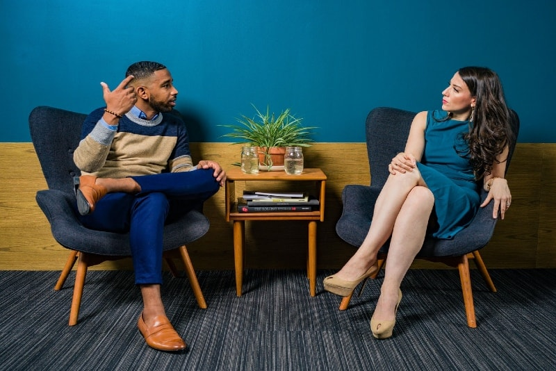 man talking to woman while sitting on chair indoor