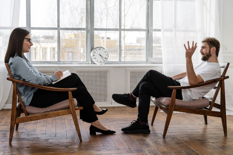 man talking to woman while sitting on chair