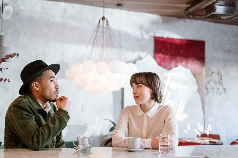 man with black hat talking to woman while sitting at table