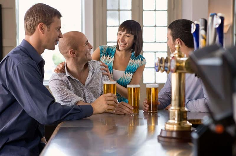 men and woman flirting in a bar while drinking beer
