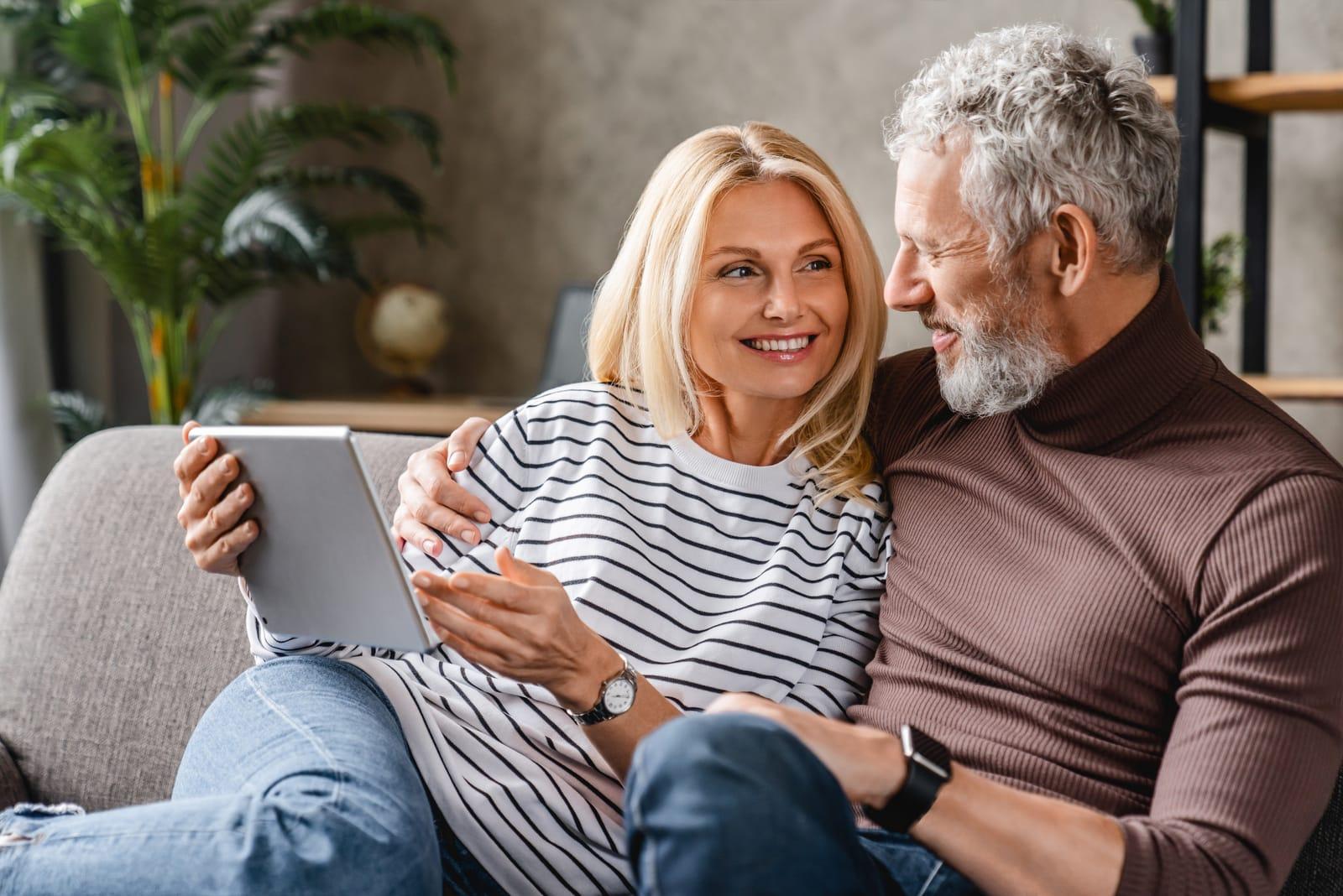 middle aged couple sitting on sofa