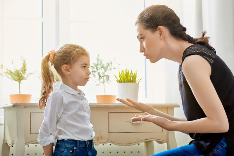 mother in black top scolding child