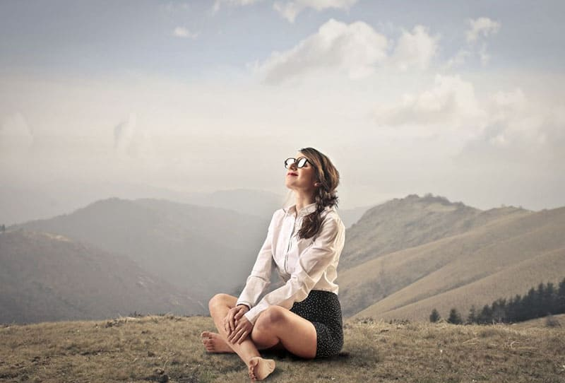 peaceful quiet woman sitting on the earth ground over the mountains