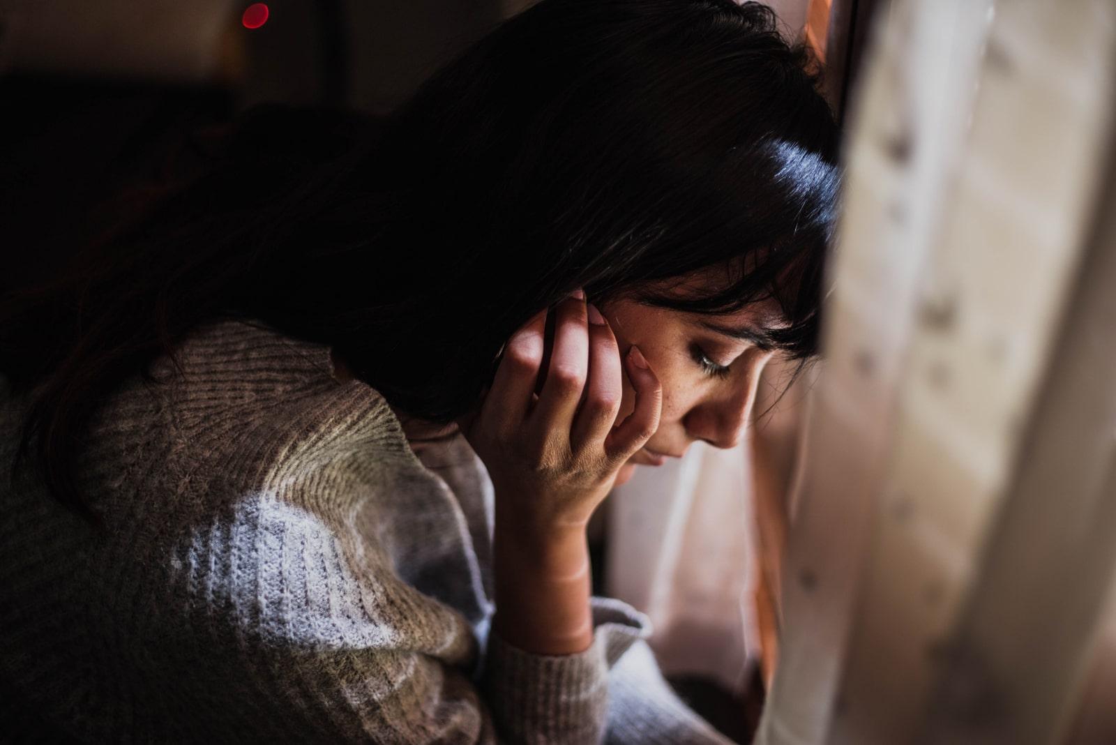 pensive sad woman sitting by the window