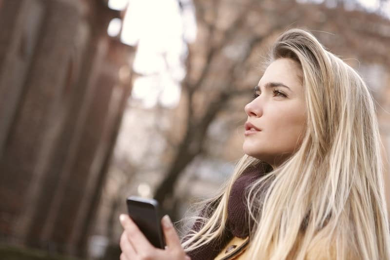pensive woman outdoors holding a cellphone