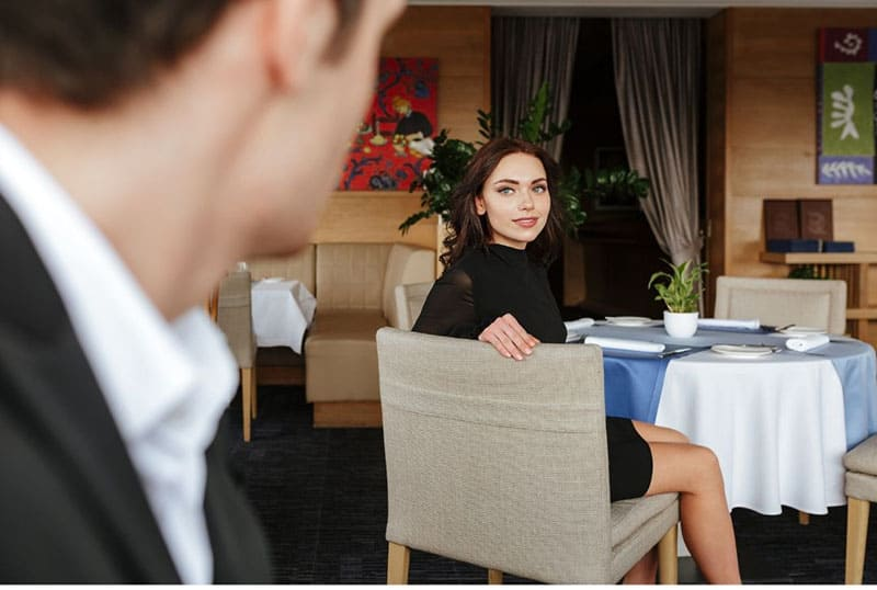 photo from the back of a man seeing a woman looking back at him sitting the restaurant's table