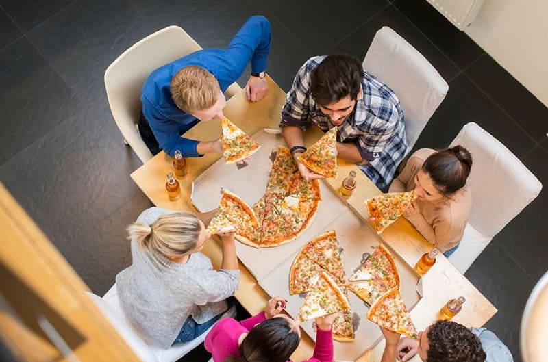 pizza party with friends with beer on a top angle