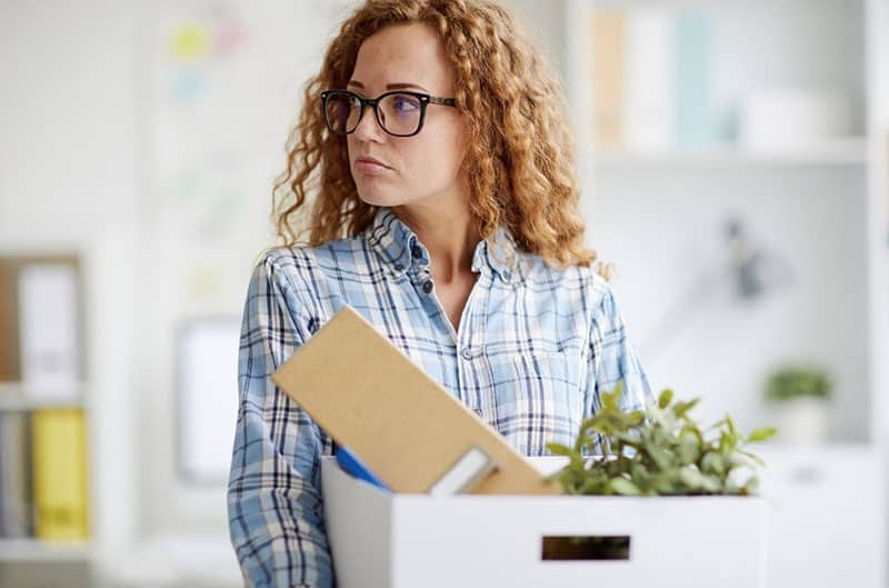 resigning young woman carrying a box filled with stuffs
