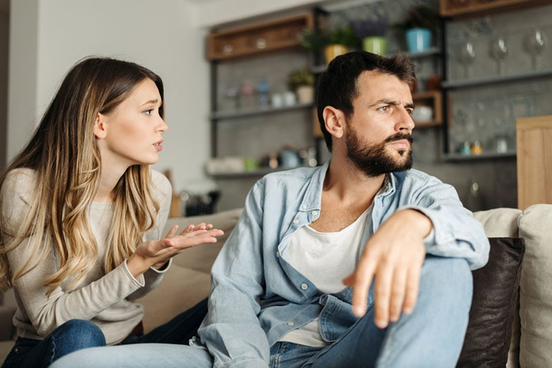 sad woman trying to talk with angry man