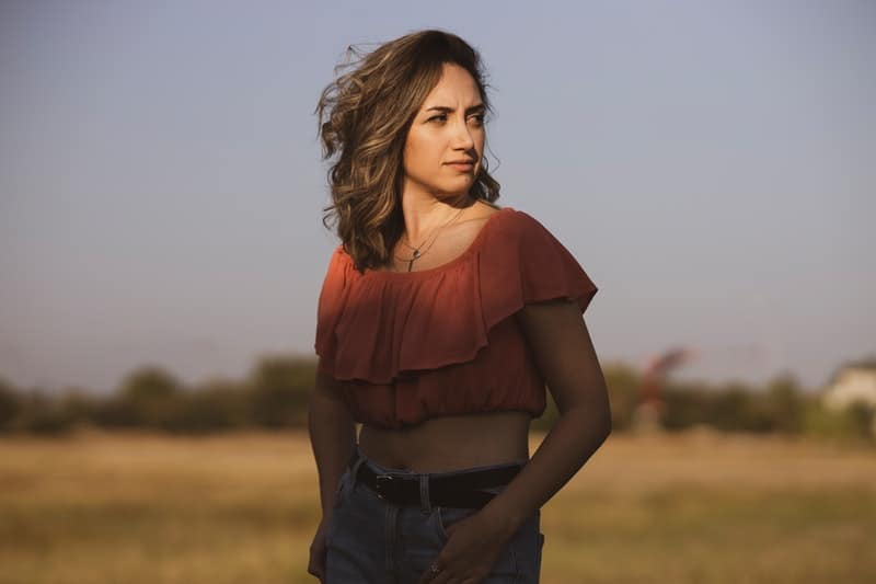 shallow focus photo of woman wearing tube standing in an open field